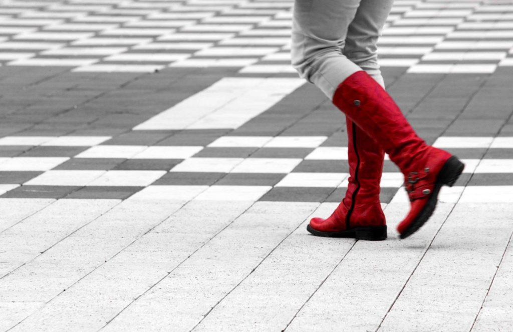 אשה במגפיים אדומות צועדת בעיר