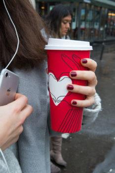 יד מחזיקה כוס משקה אדומה ועליה לב