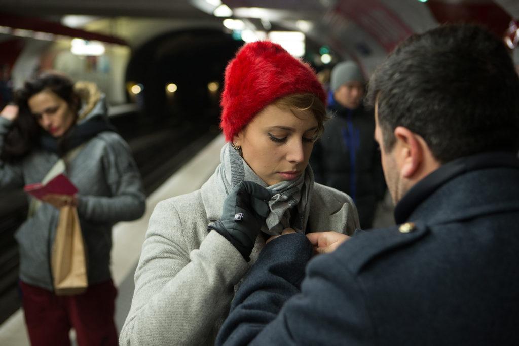 אשה בכובע צמר אדום בתחנת רכבת תחתית