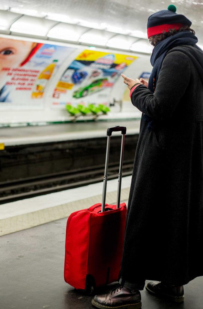 אישה מחכה עם מזוודה אדומה לרכבת התחתית
